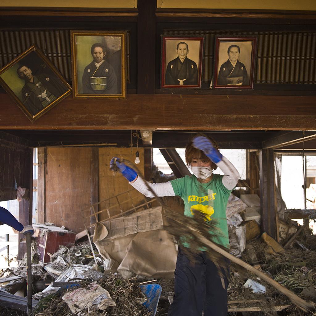 Bénévole nettoyant la maison de la famille Codama ensevelit par les eaux du  tsunami. Quartier Gamo Sendai. Avril 2011